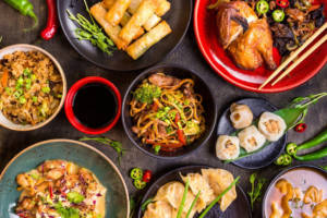 Assorted Chinese food set. Chinese noodles, fried rice, dumplings, peking duck, spring rolls. Famous Chinese cuisine dishes on table. Chinese restaurant concept. Asian style banquet